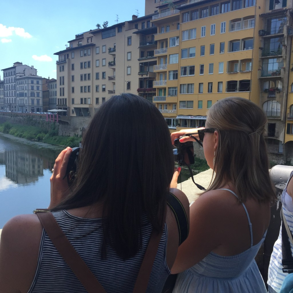 Jessica and Leah take pictures of the Arno River from Ponte Vecchio.