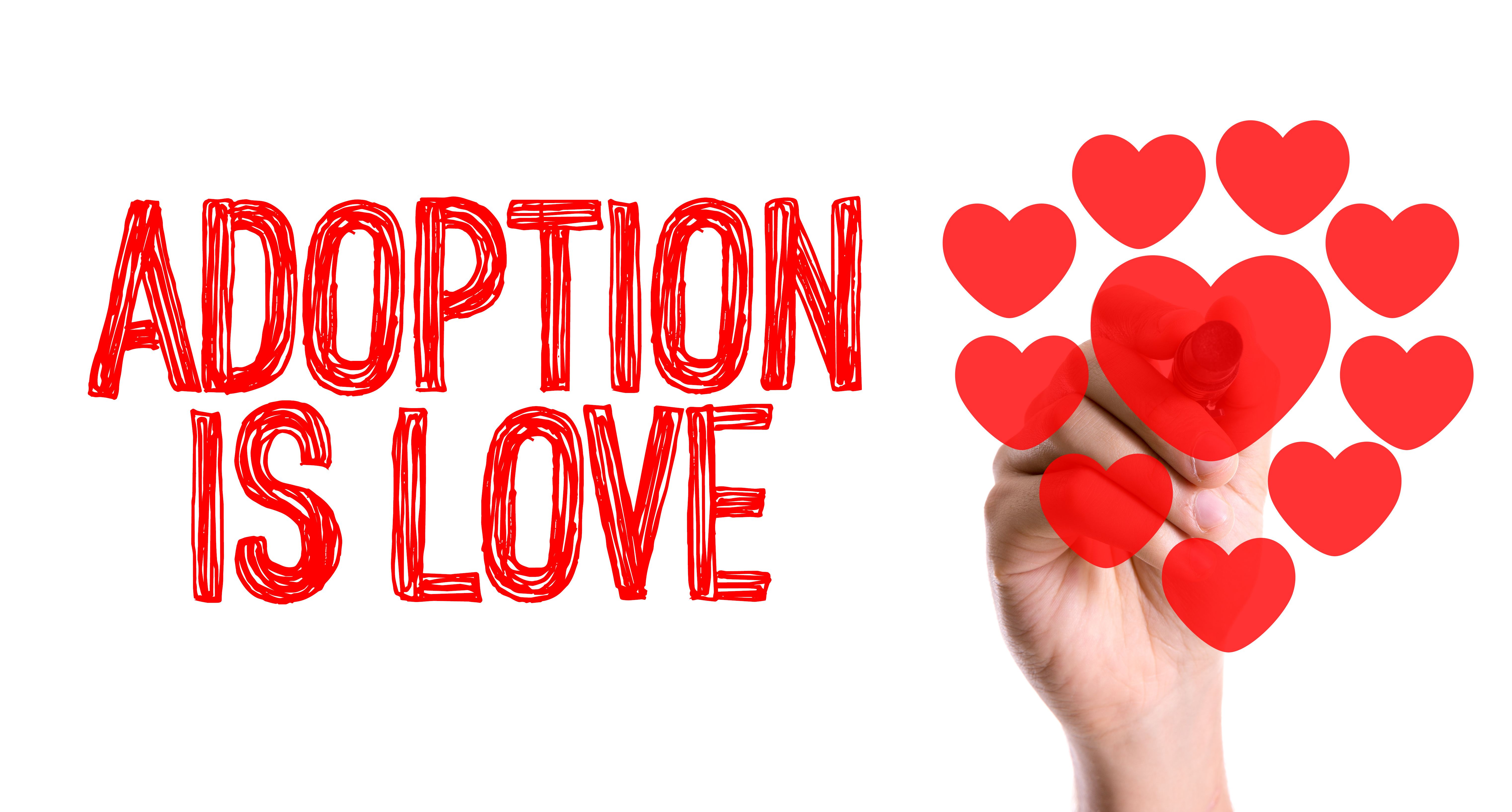 Hand with marker writing the word Adoption Is Love